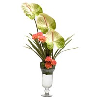 Anthuriums & peach carnations in a glass vase.