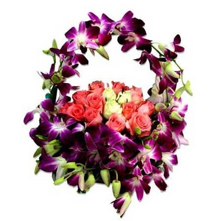 Basket arrangement of pink and white roses with purple orchids.