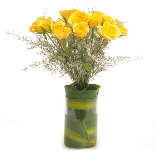 A dozen cheerful yellow roses in a glass vase.