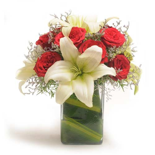 Bunch of red roses and white lilies in a glass vase.
