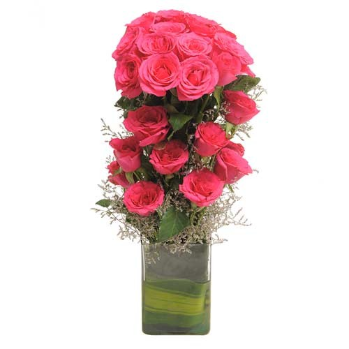 20 pink roses with fillers in a glass vase.