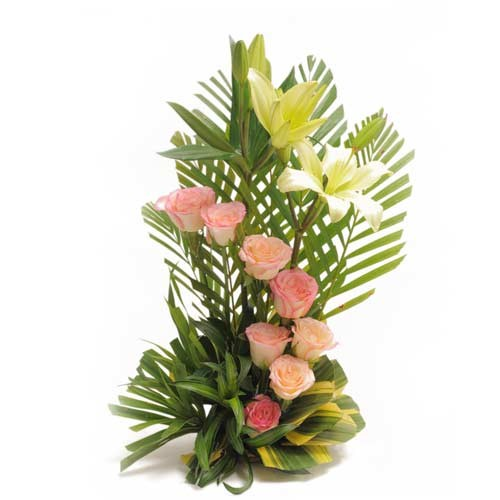 8 Pink roses and 2 white lilies arranged in a basket