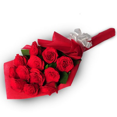 Bunch of 12 red roses wrapped in a red packing paper with white ribbon bow