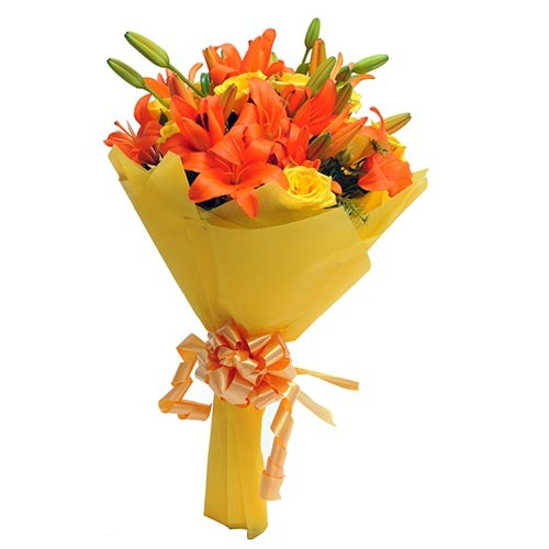 Vibrant bunch of yellow roses and orange lilies.