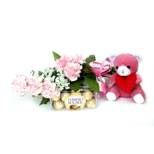 Pink carnations with chocolates and a soft toy.