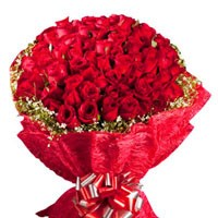 Bunch of 100 red roses with seasonal fillers.