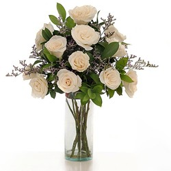 Bunch of 12 beautiful off white roses arranged in a glass vase with green fillers.