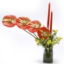 Arrangement of 4 red anthuriums with 2 candles in a glass vase.