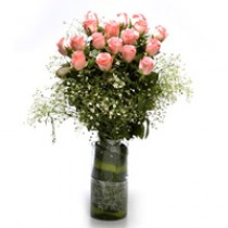 18 light pink roses in a vase.