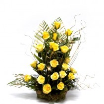 20 yellow roses arranged in a basket with dry sticks