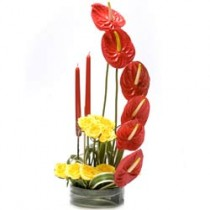 Anthuriums and yellow roses arranged in a glass vase.