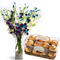 Blue and white orchids in a glass vase with a box of chocolates