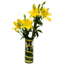 6 yellow Asiatic lilies arranged in a glass vase.