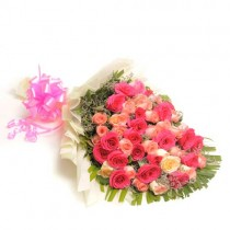 50 long stem pink and peach coloured roses in a paper packing.