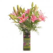 6 pink oriental lilies in a glass vase