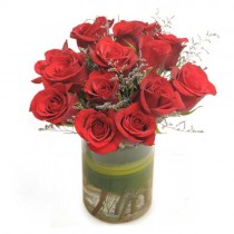 A dozen red roses in a glass vase with white fillers.