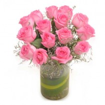15 pretty pink roses in a glass vase.