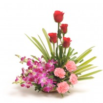 Basket arrangement of roses, orchids and carnations