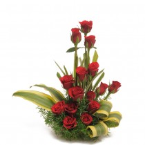 Basket arrangement of 15 long stem red roses with dracaena leaves