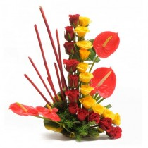 Basket arrangement of 22 yellow and red roses with 4 anthuriums