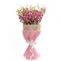 Bunch of purple orchids with white fillers wrapped in pink and white paper.