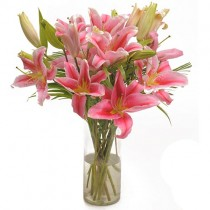 6 pink oriental lilies in a glass vase.