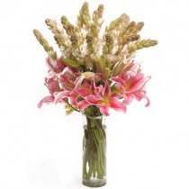Bunch of 6 pink oriental lilies and 10 tube roses arranged in a glass vase.