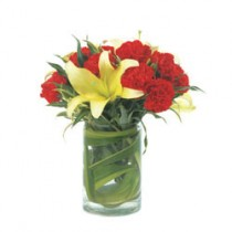 A set of red carnations and yellow lilies in a glass vase.