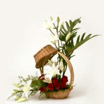 Basket arrangement of white oriental lilies and red roses.