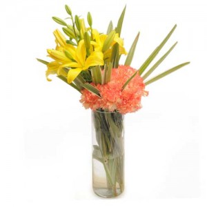 6 orange carnations and 2 yellow lilies in a glass vase.